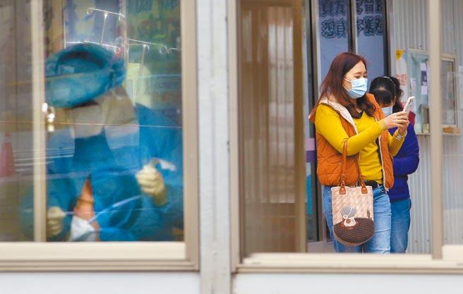 疫情指揮中心表示,針對第一線醫護人員提供每人每班、每日或每月1萬元的津貼,去年底已撥款將近25億元。圖為桃醫護理人員為民眾採檢。(范揚光攝)