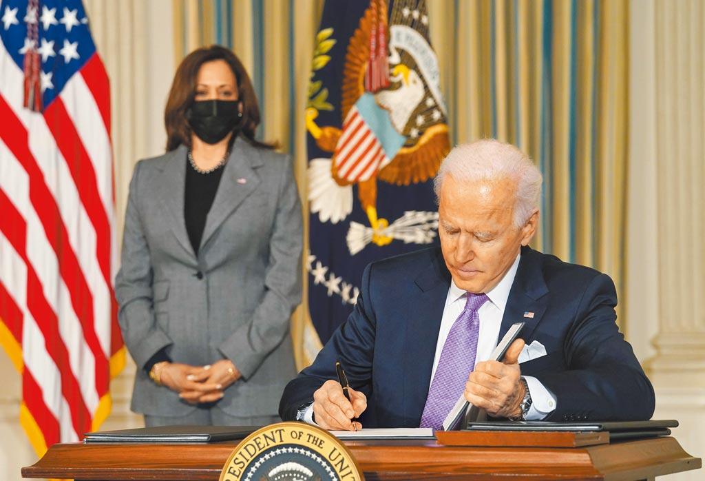 美國總統拜登26日簽署一項備忘錄,禁止聯邦政府使用「中國病毒」一詞,以避免涉及種族歧視,後方為副總統賀錦麗。(路透)