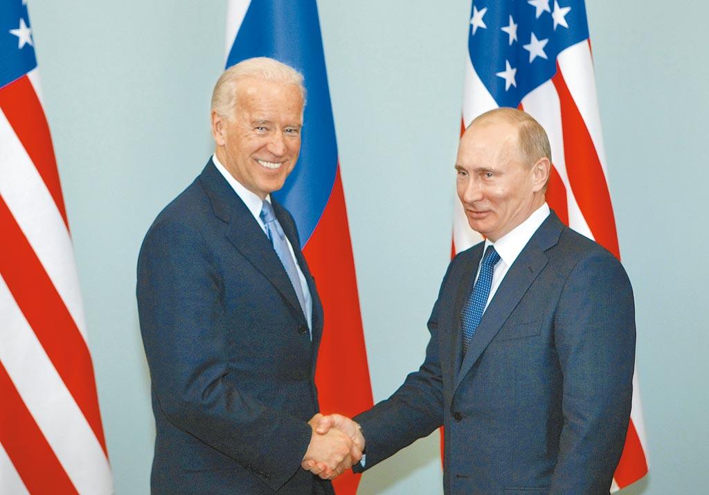 美國總統拜登(左)上任後,26日首次與俄羅斯總統普丁(右)通電話,兩人同意延長《新削減戰略武器條約》5年。圖為兩人2011年於莫斯科見面時握手。(美聯社)