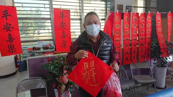 从事中古车买卖的吴宗利每年都到京城银行参加华山义卖春联活动,表示有舍就有得,买公益春联回家更平安。(程炳璋摄)