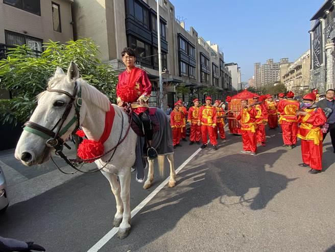 騎在白馬上的新郎倌楊竣翔,對古式迎親婚禮覺得很有意義。(盧金足攝)