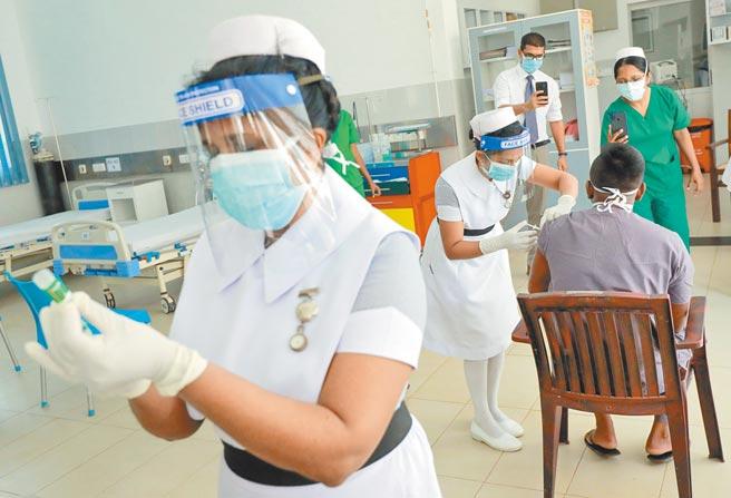 專家認為,疫苗的保護力並不是重點,畢竟是減弱而非消滅病毒,台灣最該擔心是「有沒有」的問題。圖為印度官員接受AZ疫苗注射。(路透)