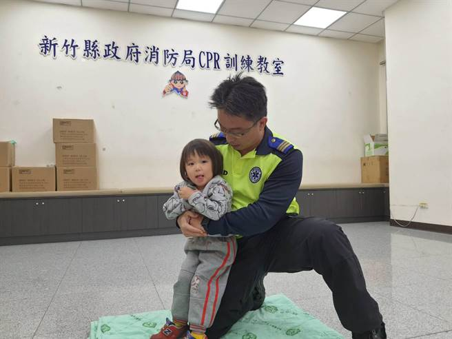 幼兒哈姆立克方式與成人相同,但需蹲下配合患者高度。(新竹縣消防局提供/羅浚濱新竹傳真)