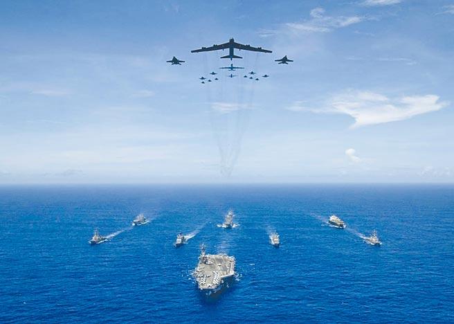 美军在关岛举行「勇敢之盾」演习中,雷根号航母舰队及B-52轰炸机、F/A-18大黄蜂等战机编队前进。(摘自美国海军官网)