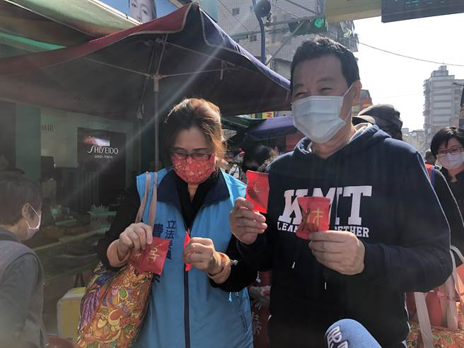 國民黨團總召費鴻泰上午偕同太太王怡心,一同到吳興市場向民眾拜早年,沿路發放春聯、印有發財字樣的餅乾。(趙婉淳攝)