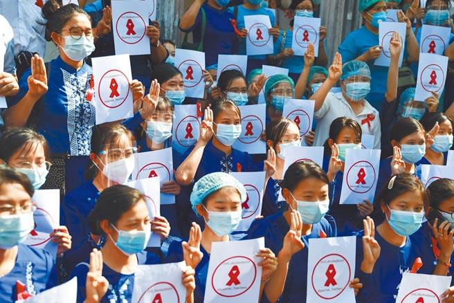 緬甸仰光教育大學的教師,5日比出反軍政府統治的三指手勢,抗議軍方發動政變。(美聯社)