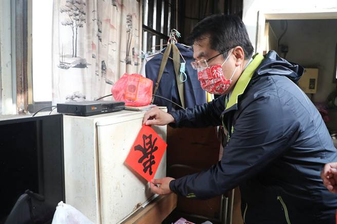 黃偉哲幫顏阿公貼上新春聯。(台南市政府提供/曹婷婷台南傳真)