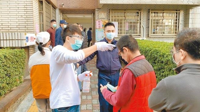 高雄罢捷投票6日一早开始,选务人员为选民量体温、喷酒精。(柯宗纬摄)