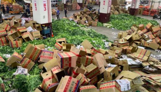 網友貼出青菜被丟棄成山的畫面,嘆「拍賣市場滿滿的菜,說不要就不要了」。(翻攝自爆廢1公社)