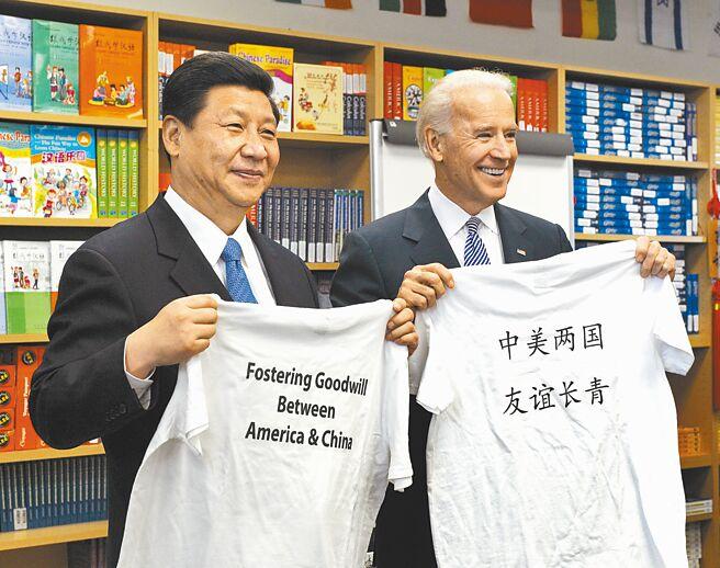 圖為2012年,習近平與拜登在美國洛杉磯參觀國際研究學習中心,相互交換學生贈送,印有「中美兩國 友誼長青」字樣的T恤。(新華社)