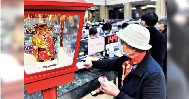 農曆新年將近,銀行營業大廳特別擺設應景財神,預祝前來辦事的民眾牛年發大財。(圖/報系資料庫)
