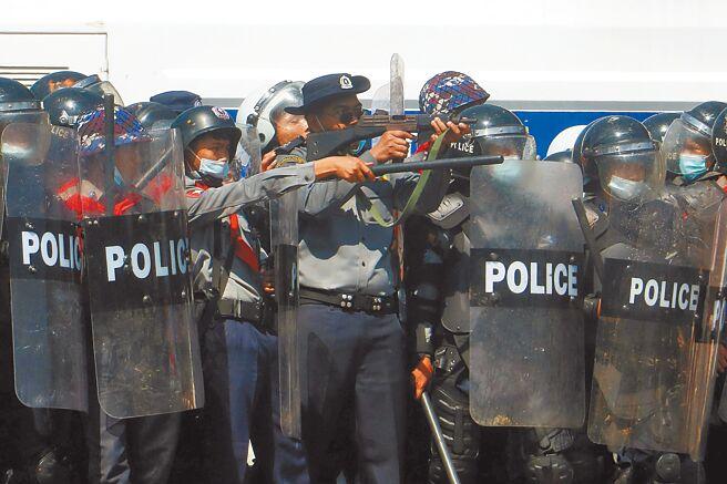 緬甸一名警察2月9日瞄準要求釋放民選領導人翁山蘇姬的抗議者。(路透)