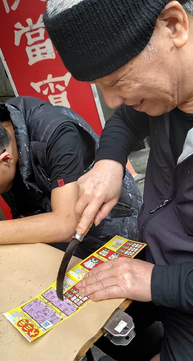 一位民眾在台北汐止街頭看到一位老伯伯用刀子在玩刮刮樂。(摘自爆廢1公社)