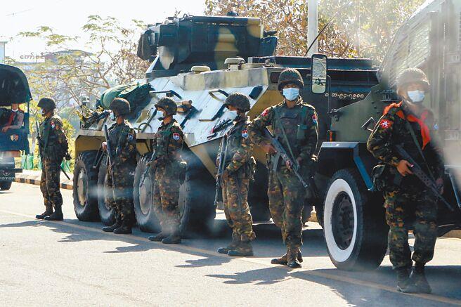 一群緬甸示威民眾15日舉著國務資政翁山蘇姬的照片及抗議軍方政變的標語牌,在首都奈比多街頭聚集,要求軍方釋放翁山等民選政府官員;有些民眾甚至在裝甲車前揮舞標語。(路透)