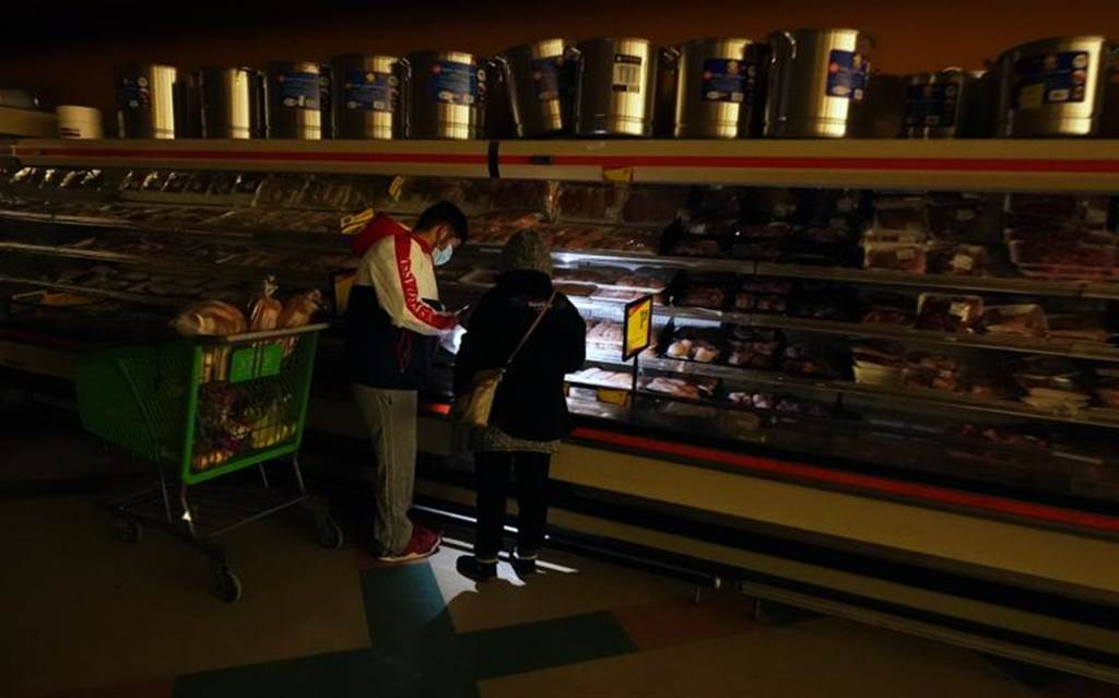 德州因暴雪导致大停电,达拉斯民众在黑暗中,只能靠手机光线找寻超市架上的生鲜。(美联社)(photo:ChinaTimes)