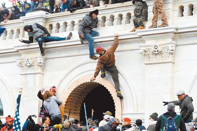 1月6日,美國時任總統川普的支持者爬上國會大廈牆壁抗議。(路透)