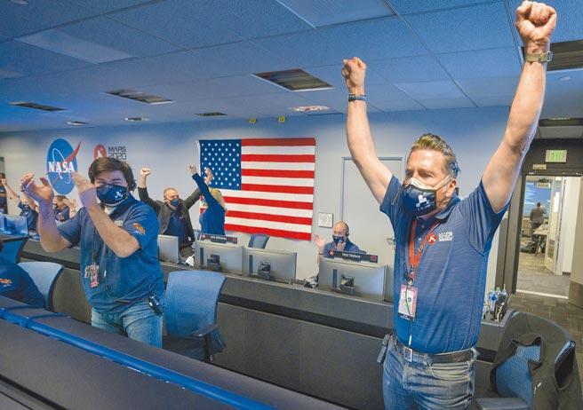 美國國家航空暨太空總署(NASA)的火星探測器「毅力號」,18日安全登陸火星表面。加州任務控制中心的團隊成員,在見證歷史的瞬間興奮歡呼。(美聯社)