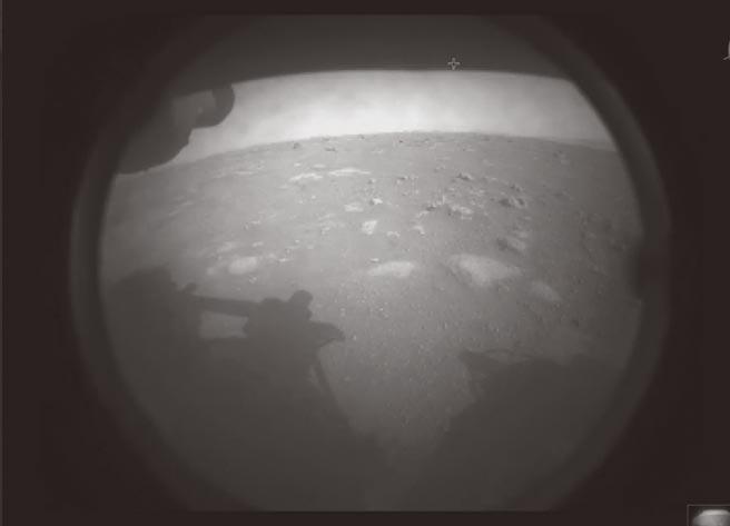 美國國家航空暨太空總署(NASA)的火星探測器「毅力號」,18日安全登陸火星表面。毅力號隨後也傳回凹凸不平的火星表面寫真,還可看見火星車的影子。(美聯社)