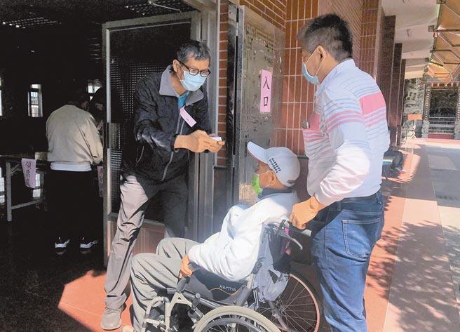 全台基層農會改選21日舉行,農會會員到岡山區的投開票所投票,選務人員為會員量測額溫。(林瑞益攝)