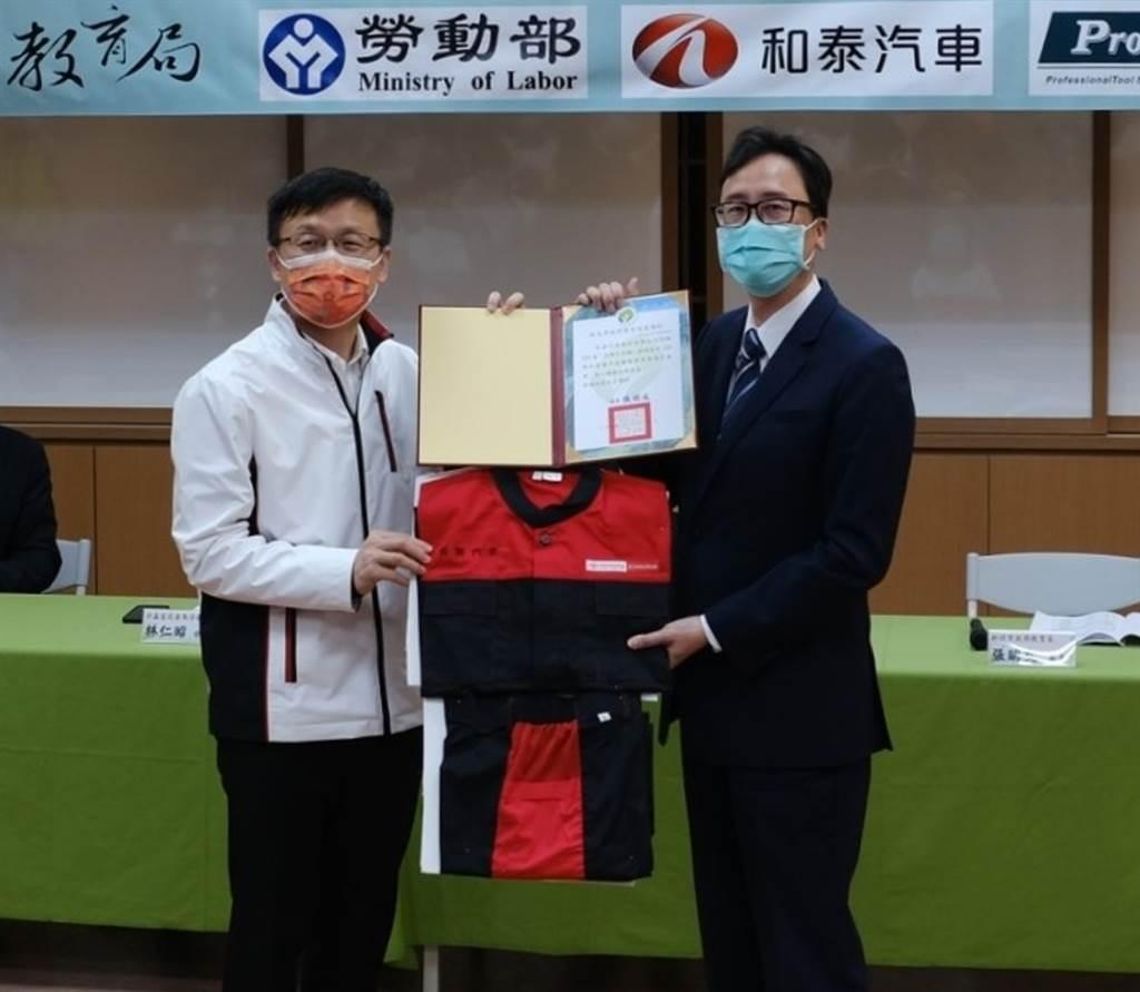 新北市教育局局長張明文(左)、和泰汽車經理李建興(右)進行捐贈儀式。