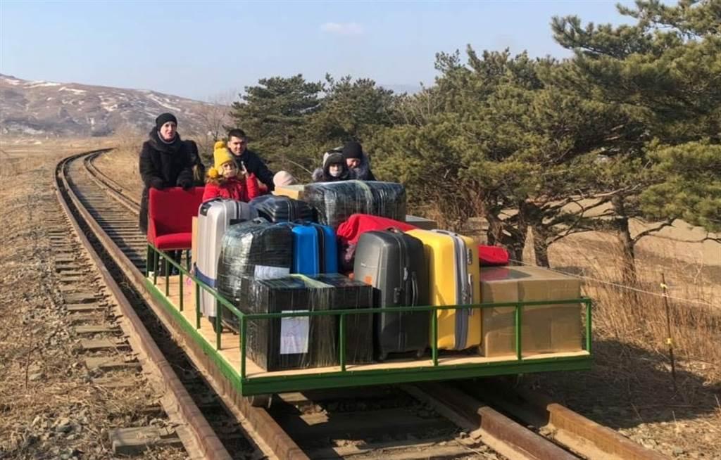俄罗斯大使馆三等秘书索罗金(Vladislav Sorokin)推着轨道台车,带着成堆行李和同僚家属,历经1公里的旅程后,才终于穿越边境返国。(路透)(photo:ChinaTimes)