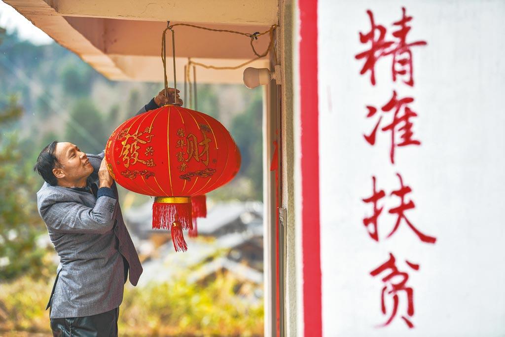 大陸貴州省獨山縣影山鎮桑麻村的脫貧戶羅幸幫,正在新居前修整燈籠。(新華社)