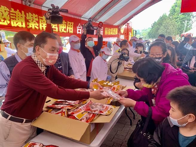 紫南宮主委莊秋安(左),發送丁酒(麻油雞)冷凍調理包給民眾。(廖志晃攝)