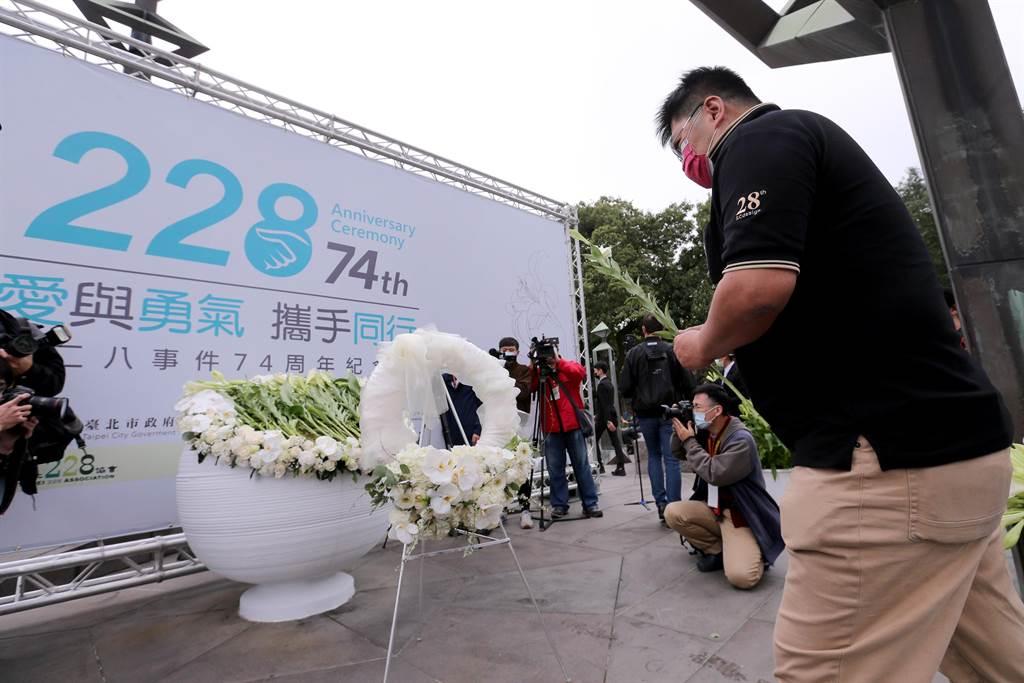 台北市政府28日舉辦228事件74周年紀念會,出席民眾將百合花放在紀念碑文上,弔念當年犧牲生命的罹難者。(黃世麒攝)