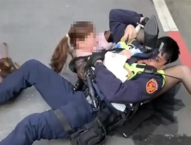 一名曹姓婦人不滿車輛被警方拖吊,不願配合遭警方制伏在地,卻還對警察拳打腳踢,打完警察後還癱地痛哭。(翻攝台中踢爆網)