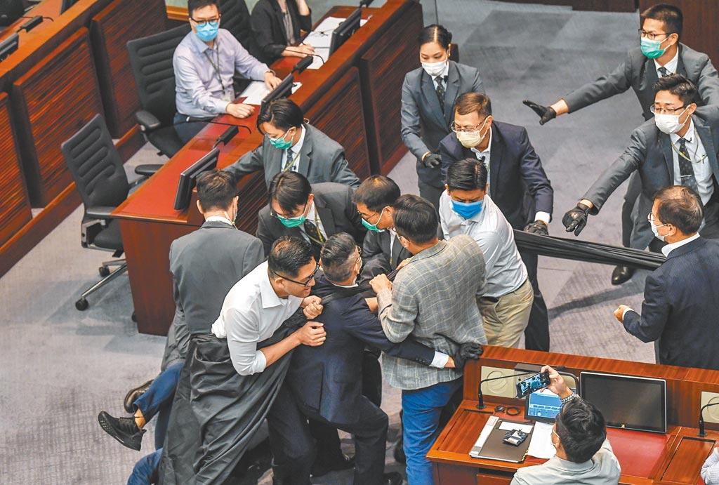 綜合香港媒體消息,大陸全國人大擬授權通過改革香港選舉制度方案的決定。圖為日前香港立法會內務委員會舉行主席選舉,反對派議員包圍主席台。(中新社資料照片)