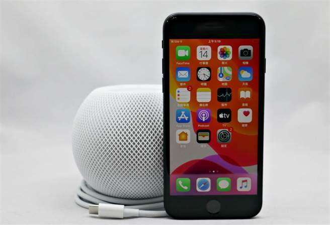 HomePod mini與iPhone SE(第二代)對比,可以看見體積真的相當小巧。(黃慧雯攝)