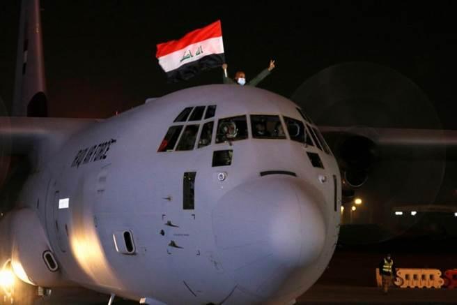 運載疫苗的運輸機抵達伊拉克,飛行員舉起國旗慶祝。(圖/路透社)