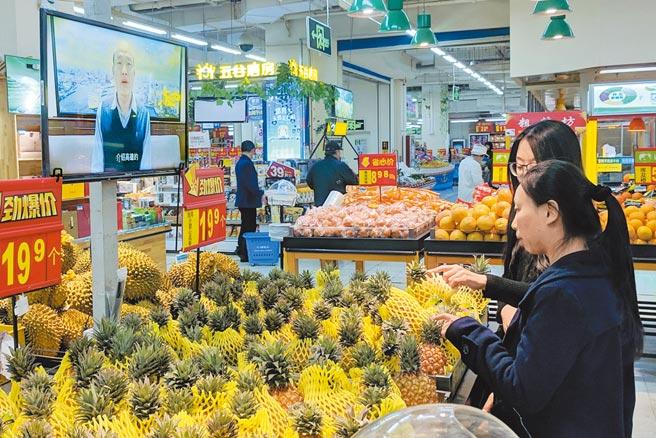 台商透露,大陸連鎖超市這2天聯繫他詢問進貨時可否拆下「原產地台灣」的腰牌,避免消費者看到不敢買。圖為北京市民在大型超市選購來自台灣的鳳梨。(中新社)