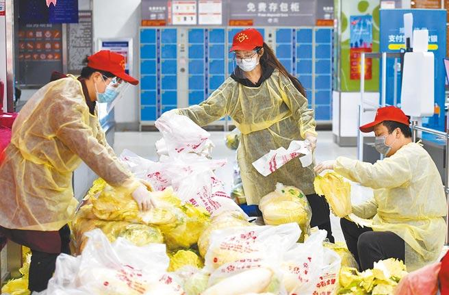 大陸自去年底起,主要城市商場禁用塑膠袋。圖為大陸義工將物資裝入塑膠袋。(新華社)