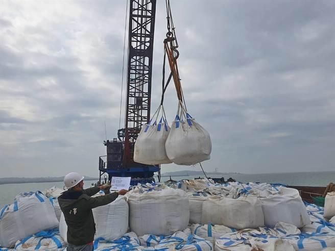 大、小金門海底輸水海管不明原因上浮,水廠雇工在海管上浮兩端進行沙包保護。(金門自來水廠提供)