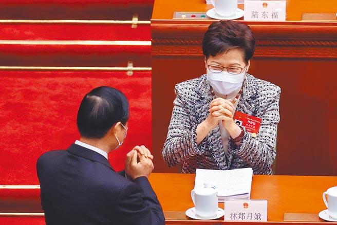 3月5日,中共第十三届全国人民代表大会第四次会议在北京人民大会堂开幕,香港特首林郑月娥(右)列席开幕式。(中新社)
