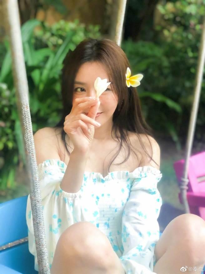 秦嵐把花朵插在秀髮上,而身穿一字領上衣的她,香肩和美肌全都露。(圖/取材自秦嵐微博)
