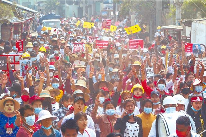 在緬甸第2大城曼德勒,示威民眾手持標語走上街頭,要求釋放翁山蘇姬等文人領袖,還有許多人高舉象徵反抗極權的三指手勢。(美聯社)