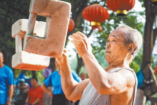 今年是大陸將人口老齡化問題升級為國家戰略的第一年。圖為北京一長者在用石鎖健身。(新華社)