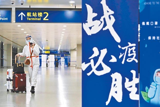 大陸率先推出防疫護照,有助於大陸民眾出國,提供國際認證。圖為出境旅客在浦東機場內,前方寫著「戰疫必勝」標語。(中新社)