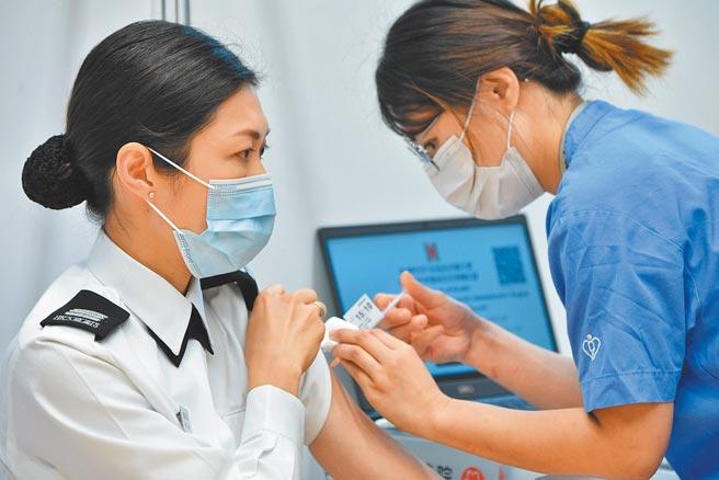 香港3月8日,約100名優先接種組別人士在設于中山紀念公園體育館的社區疫苗接種中心接種復必泰疫苗。。圖為一名入境事務處人員(左)接種疫苗。(中新社)