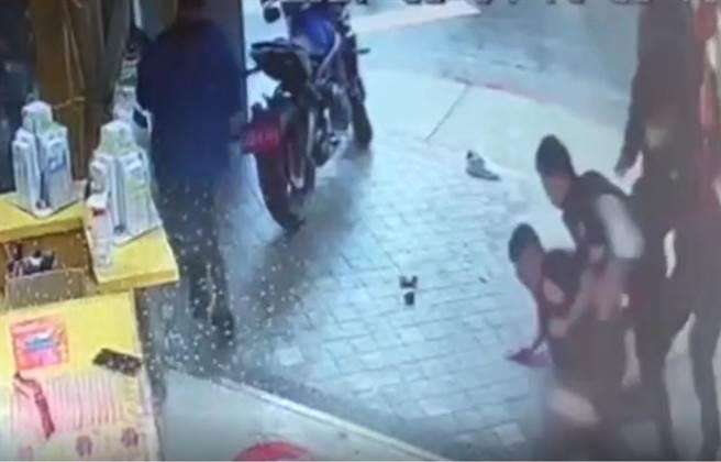 騷擾彩券行討錢,男用胸撞警遭噴辣椒水壓制在地。(翻攝影片)