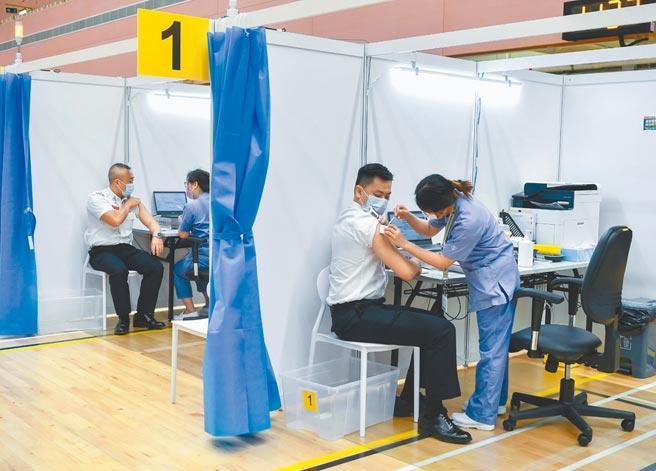 截至11日,香港兩周內已有4起疑似接種新冠疫苗後死亡的個案。圖為港府消防處人員接種疫苗。(中新社)