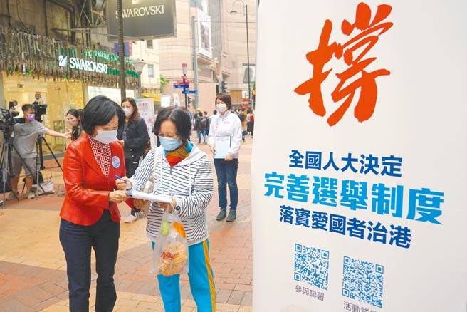 3月14日,在香港銅鑼灣街頭的「撐全國人大決定 完善選舉制度」街站,眾多建制派立法會議員和區議會議員在街頭收集市民簽名,支持完善香港選舉制度,落實「愛國者治港」。(中新社)