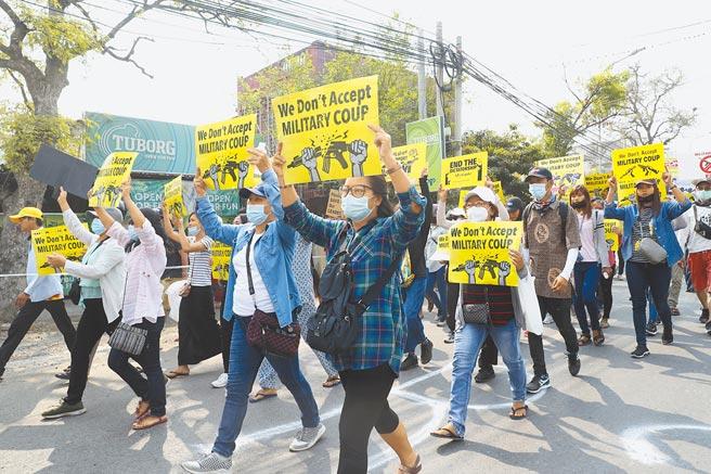 緬甸軍政府昨天緊急宣布擴大在仰光戒嚴的範圍。台廠昌億也在暴亂中遭池魚之殃。圖為緬甸反對政變的民眾在瓦城舉標語示威。(美聯社)