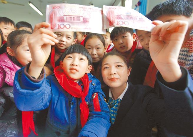 鼓勵年輕人理財有助縮短所得差距。大陸不少小學,已有傳授小朋友理財。圖為浙江省諸暨市諸暨農商銀行員工來到荷花小學,教學生如何識別假鈔,如何合理使用壓歲錢。(新華社)