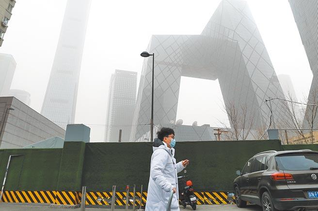 北京市民在沙塵天氣中出行。背後央視新大樓有如在霧中。(中新社)