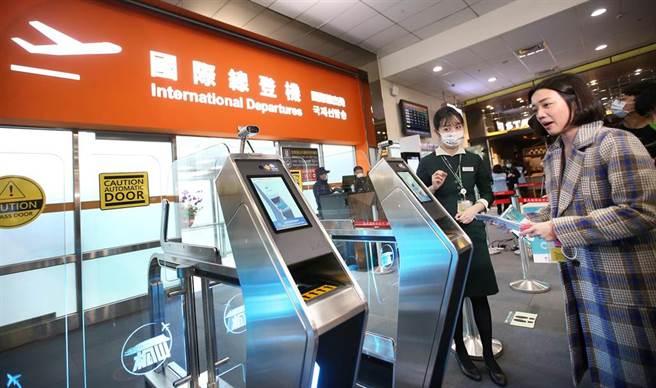旅客持護照及登機證通過e-CHECK閘門。(范揚光攝)