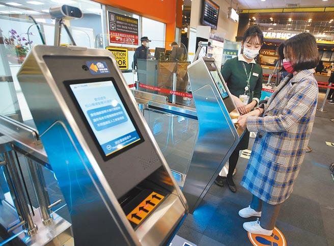 松山機場「3e PASS」智慧通關系統24日開始試辦,交通部長林佳龍23日視察時表示,藉由科技不僅能降低查驗人力的負擔及不必要的接觸,也營造智慧機場的國門形象,圖為旅客持護照及登機證通過e-CHECK閘門。(范揚光攝)