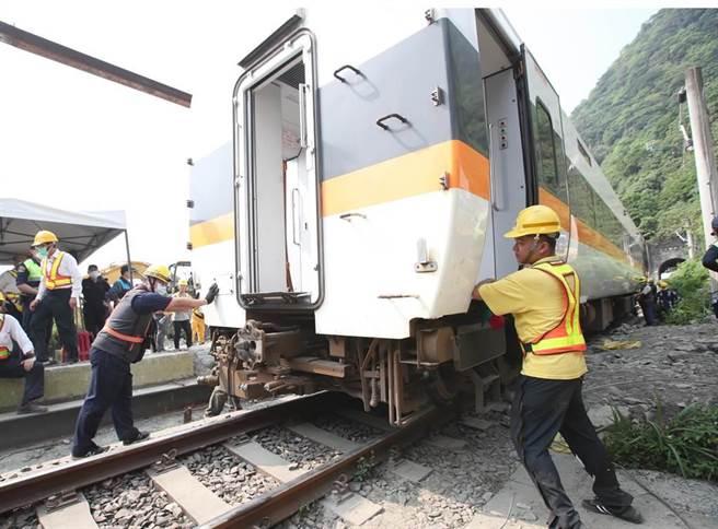 台鐵太魯閣號在花蓮撞上工程車出軌意外,3日現場工作人員開始吊起第二節車廂,放回正常的軌道慢慢與一號車廂連接後拖離現場。(鄭任南攝)